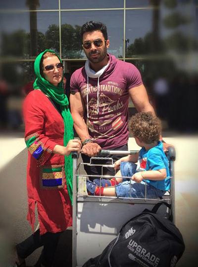 عکس خانوادگی روناک یونسی با چرخ حمل بار در محوطه فرودگاه